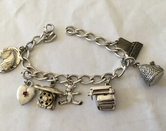 Sterling charm bracelet with 3 deminsonal charms Typewriter , Beehive, Bear, Dial phone, Heart, Horseshoe with Horse and ins co shilouette