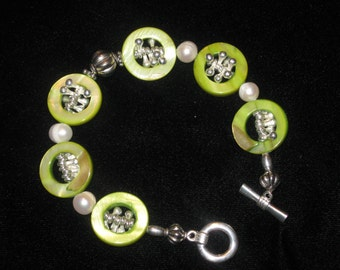 Apple green shell beads with silver dangle beads inside, fresh water pearls and silver bead toggle clasp bracelet