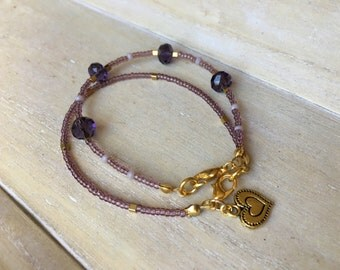 Set of two bracelets, purple miyuki beads with golden accents, purple faceted beads and heart charm.
