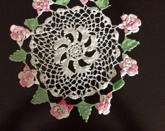 Vintage doily with shades of pink roses and green leaf border