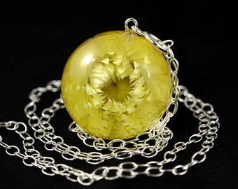 Resin pendant with natural everlasting garden (Helichrysum bracteatum) in large sphere on a silver chain. Sphere 3.4 cm. Chain 80 cm.
