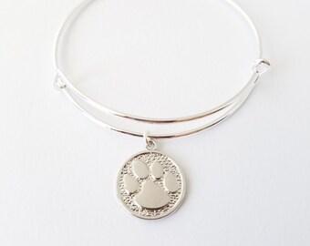 Shiny silver plated dog paw print charm on a silver plated bangle bracelet