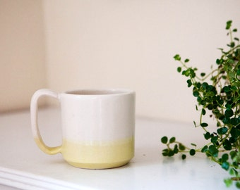white and yellow stoneware ceramic coffee mug