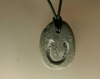 Horseshoe engraved onto beach pebble fastened with a leather adjustable necklace