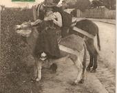 Vintage French Real Photo postcard, Romancing Lady and man riding donkeys kissing, vintage postcard