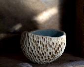 Handmade decorative bowl with textured exterior and aqua crackle glazed interior.