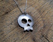 Sterling silver skull pendant with asymmetrical eyes. Cartoon skull with chain