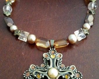 Ornate bronze cross with orange gems and beaded necklace