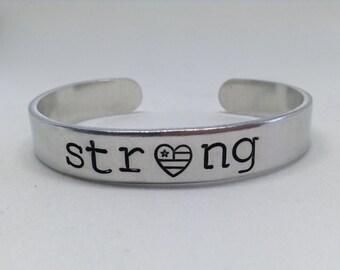 Strong, America, patriotic cuff bracelet, flag symbol, large print, hand stamped