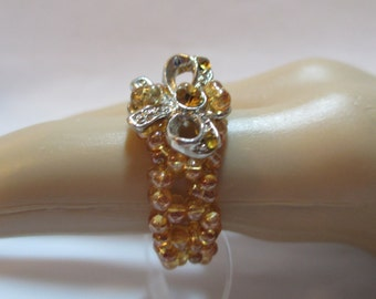 Ring with yellow beads with silver metal bow with crystals on stretchy cord size 7