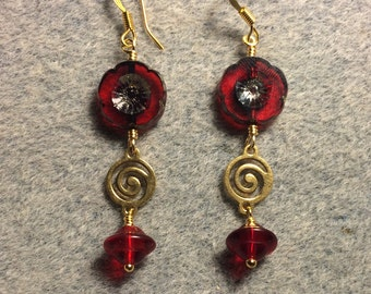 Translucent red Czech glass pansy bead dangle earrings adorned with gold swirly connectors and translucent red Czech glass Saturn beads.