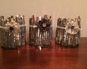 Set of three rustic glass candle holders with flowers, twigs and twine