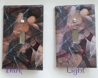 Single toggle light switch plate collage of river rock with skeletal leaves overlay, peaceful, beautiful, decorative switch plate