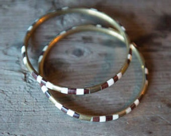 10 dollars with purchase, set of 2 wood/shell/brass bangles.