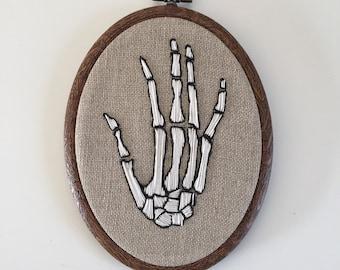 Embroidery hoop, skeleton hand