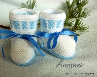 Knitted baby booties, knitted baby shoes in   white , decorated with blue ribbon