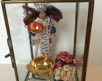 Set of a Glass Jewelry Box with a little chef, a brass pot, and flowers