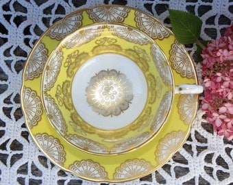 Paragon; Footed tea cup and saucer, yellow, white and gold