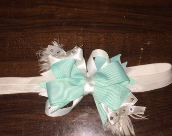 Stacked hair bow with feathers behind it