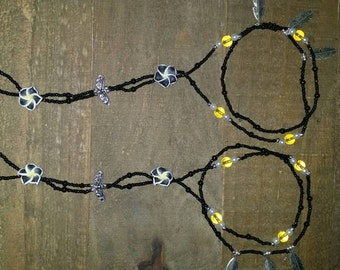 Black and yellow double twist barefoot sandals with feather charms