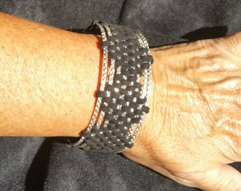 Silver bangles weaved together with black leather.