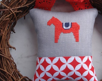 Cross stitched ornament with motif of horse.