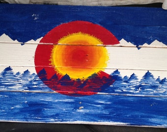 Colorado flag with mountains, trees, and sun.