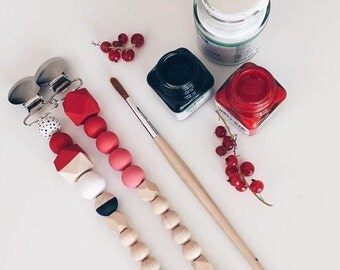 Hand-painted dummy with geometric wooden beads in red patterned or the ombre look