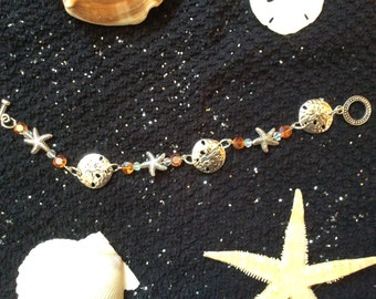 Bracelet embellished with sand dollars and starfish... Clear and orange crystals. 7 and a half inches long.