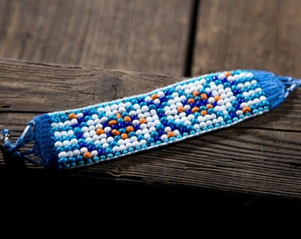 Owls eyes. Beaded braceled. White, blue and orange beads. Cotton thread, clasp handmade, not ideal.