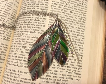 Silver tone feather pendant with enamel coloring.