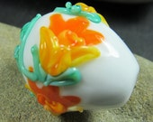 White Easter egg focal bead with daffodils in bloom