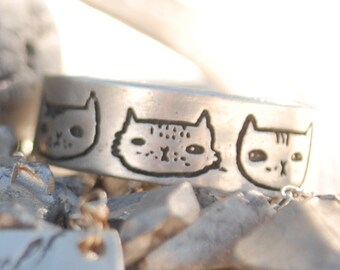 Illustrated wide band CAT HEADS ring, illustrated by Gemma Correll, eco-friendly sterling silver. Handcrafted by Chocolate and Steel