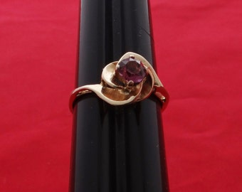 Vintage new old stock NOS size 9 gold tone ring with purple rhinestone in unworn condition