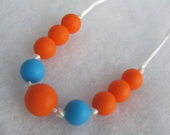 Silicone Teething Necklace. Blue and orange. Silk cord. Snap safety closure.