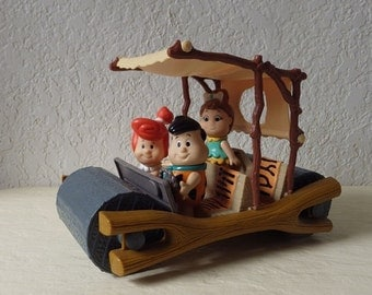 Yabba Dabba Doo! Fred, Wilma and Pebbles Flintstone out cruising in their Flintmobile using Fred's Peddle Power.