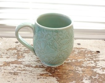 Stoneware Cup with a Lacey Pale Green Flower and Bird Design, Hand Carved