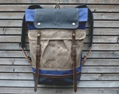 Waxed canvas backpack with folded top and waxed canvas shoulderstrap and bottom