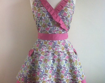 Retro apron, earth tone coloured leaves on a white fabric with a pink bow,  fully lined.