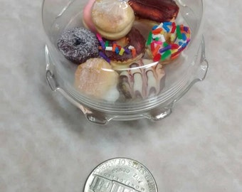 Miniature donuts under glass dome. Top and donuts can be removed.