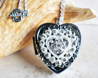 Music box locket, heart shaped locket with music box inside, in silver tone with heart shaped rhinstone setting on front cover.
