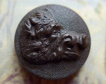 Boars head button, vintage. It features the profile head of a Boar, stippled background, concave, a hunting button, prob. bakelite. c1950's.