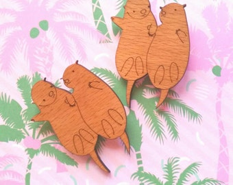Drifting together. Two Otters holding hands laser cut wood wooden brooch pin lapel badge