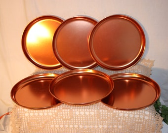 Six 9 inch copper colored aluminum plates, in great condition