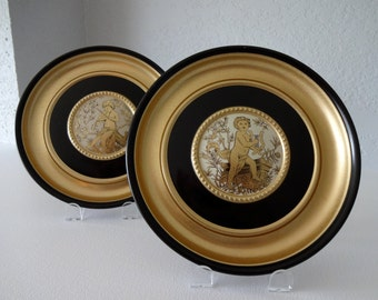 Pair of black and gold plaques illustrated with cherubs playing music