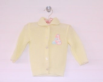 Vintage baby sweater, yellow knit with horses on the front. five buttons up the front, Childwise size about 3-6 months