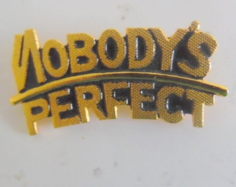Nice gold tone pin/ brooch.  It says: Nobody's Perfect