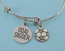 """Goal Digger bangle bracelet in stainless steel with silver plated pewter soccer ball and word charm that reads """"Goal Digger""""."""