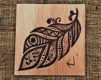 Patterned feather pyrography wood art