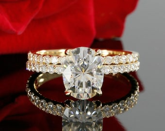 9x7mm Oval Forever One Moissanite and Diamond Solitaire Engagement Set in 14K Yellow Gold (avail. white gold, rose gold and platinum)